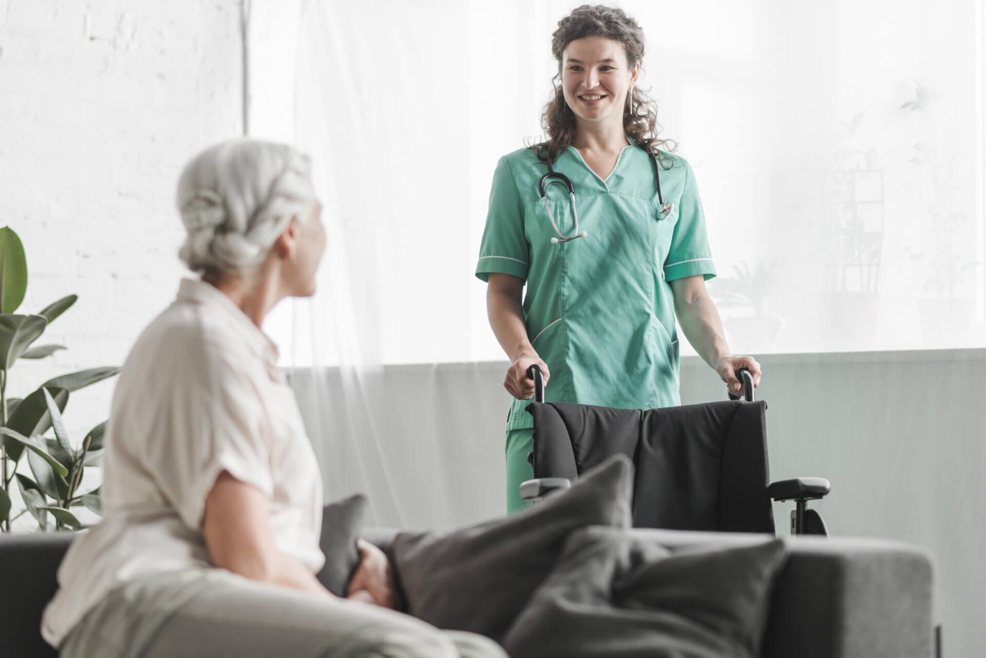 senior-woman-looking-smiling-female-nurse-with-wheelchair (1) (1)