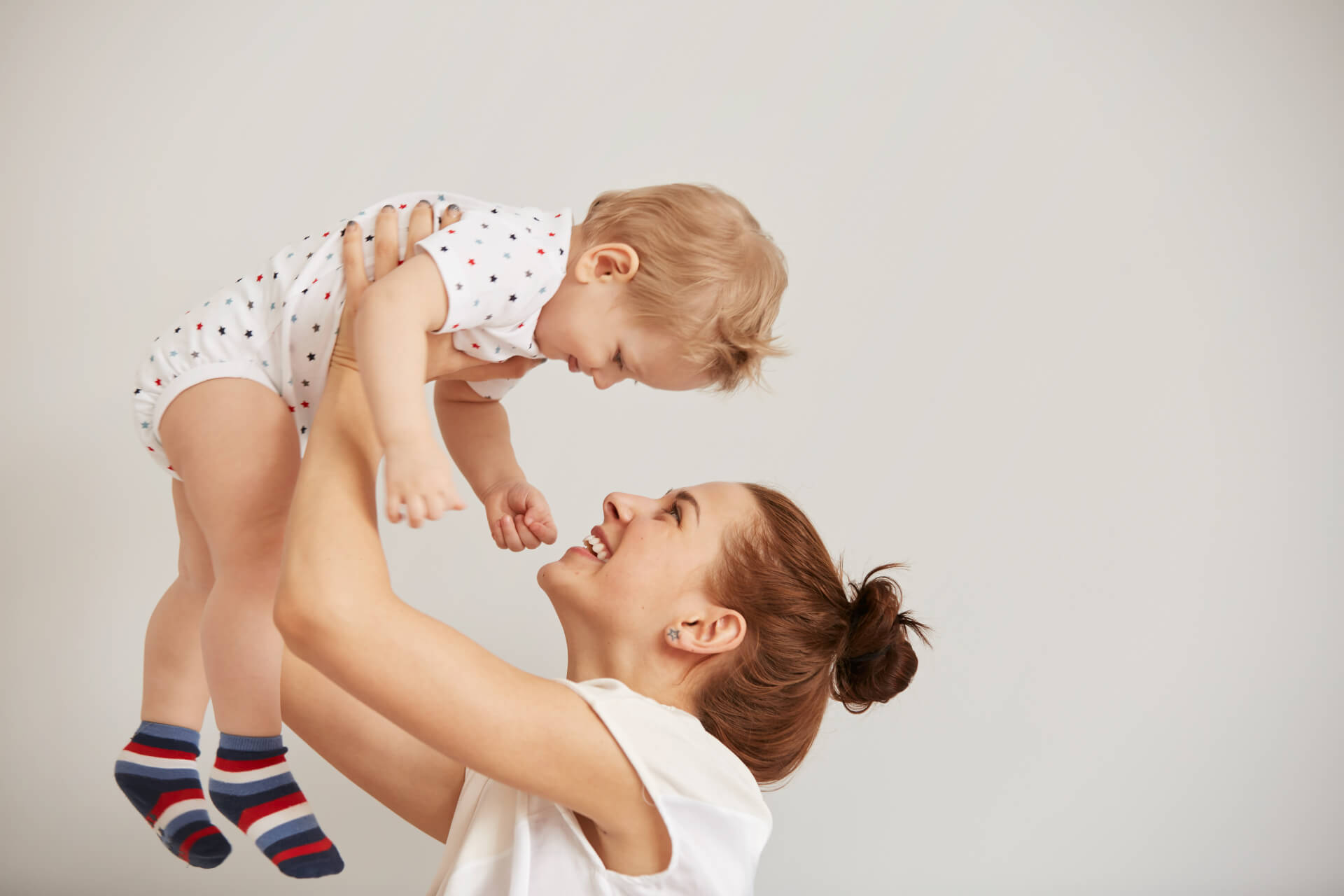 young-mother-playing-with-her-little-baby-bed (1) (1)